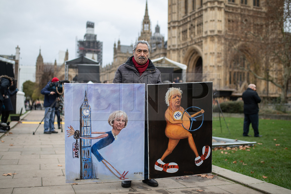 © Licensed to London News Pictures. 10/12/2018. London, UK. Satirical artist Kaya Mar poses with his artworks as anti-Brexit demonstrators protest alongside pro-Brexit demonstrators outside the Houses of Parliament. Tomorrow MPs will vote on British Prime Minister Theresa May's EU withdrawal deal. Photo credit : Tom Nicholson/LNP