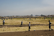 School children in Dandora, Kenya, playing in a field, which backs out on to a large dumpsite. The dumpsite and its pollution causes many health problems, which disrupts their education.