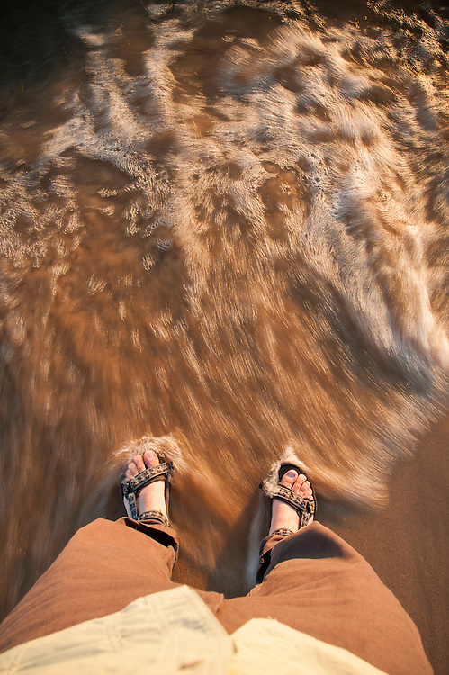 Point of view shot of feet in sandals as waves wash over them.