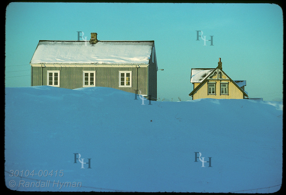 Old farmhouses at Arbaer Folk Museum tucked behind big snowbank catch light of sunrise at noon.* Iceland