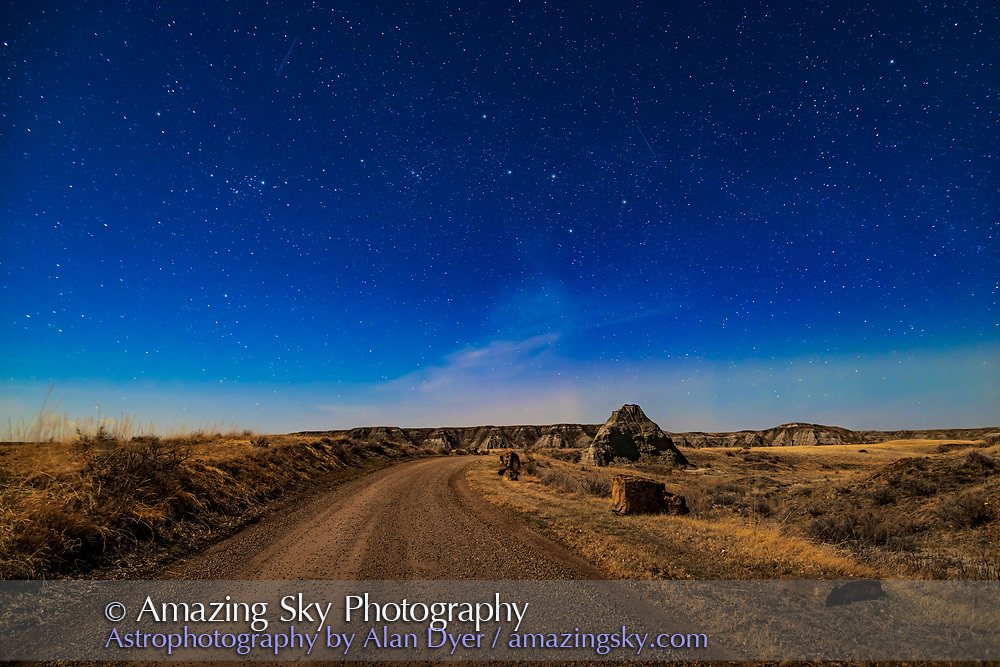 The autumn constellations of Cassiopeia (centre) and Perseus (left) low in the north in the moonlight at Dinosaur Provincial Park, April 20, 2021. From this latitude of 51° N they skim low across the north on spring nights. The Moon was at first quarter phase off frame at top left.<br /> <br /> This is a stack of 4 x 20 seconds for the ground and a single 20-second exposure for the sky, all with the Sigma 24mm Art lens at f/2.8 adapted to the Canon EOS Ra camera at ISO 800. All untracked.