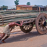 A man pushes a cart loaded with bamboo up a road in Dhaka, Bangladesh.
