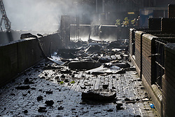 © Licensed to London News Pictures. 14/06/2017. London, UK. A walkway is filled with debris directly under Grenfell Tower on the Lancaster West Estate -  scene of a huge fire in west London. The blaze engulfed the 27-storey building with 200 firefighters attending the scene. A number of fatalities have been reported. Photo credit: Peter Macdiarmid/LNP