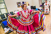 27 JUNE 2012 - GLENDALE, AZ:  CARLINDA REBELO, 71 years old, twirls in her colorful dress during rehearsal for the Senior Fiesta Dancers at the Glendale Adult Center, in Glendale, AZ, a suburb of Phoenix. Dancing as a part of workout regimen is not unusual, but the Senior Fiesta Dancers use Mexican style folklorico dances for their workouts. The Senior Fiesta Dancers have been performing together for 15 years. They get together every week for rehearsals and perform at nursing homes and retirement centers in the Phoenix area once a month or so. Their energetic Mexican folklorico dances keep them limber and provide a cardio workout.   PHOTO BY JACK KURTZ