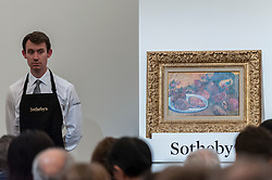 "© Licensed to London News Pictures. 24/06/2015. London, UK. A Sotheby's technician shows Paul Gauguin's ""Nature morte aux mangos"", which sold for a hammer price of £10,200,000, within its estimate. Sotheby's Impressionist & Modern art evening sale realised a total of £178.6m, the second highest total for any sale ever held in London.  Photo credit : Stephen Chung/LNP"