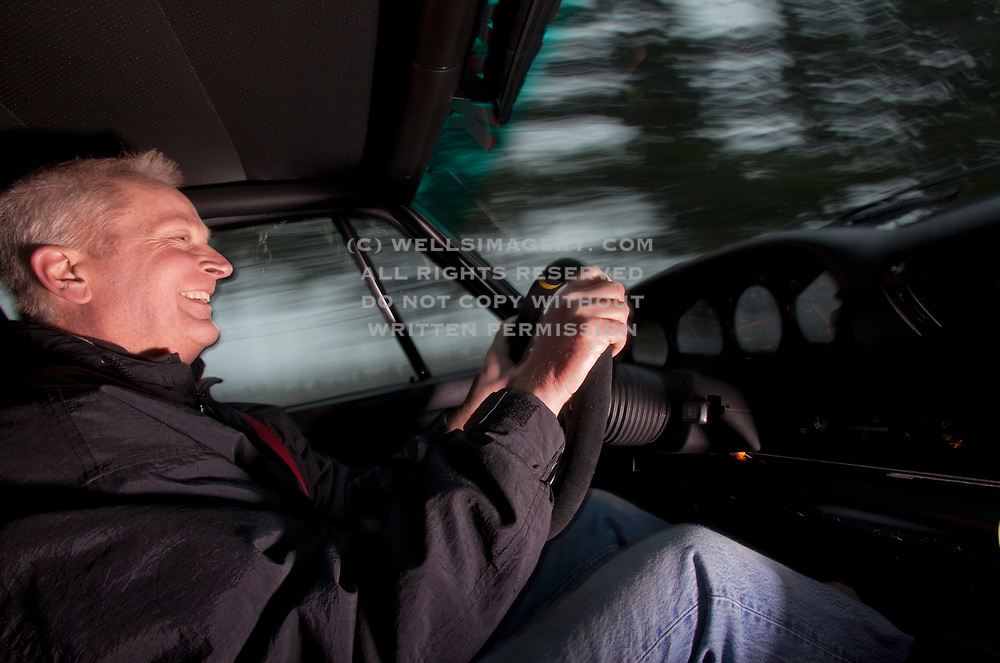 Image of a man driving a 1990s Porsche 964 in Washington state, Pacific Northwest by Randy Wells