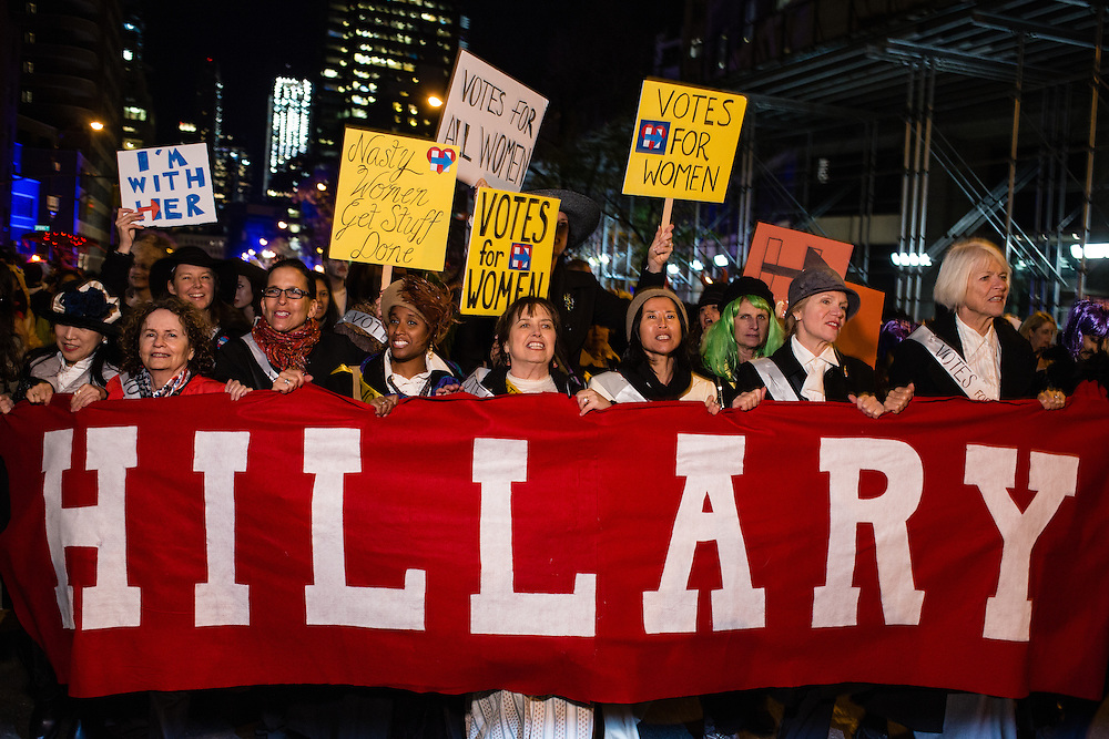 """New York, NY - 31 October 2016. Marchers in support of Hillary Clinton marrch behind a banner that simply reads """"Hillary"""" in the annual Greenwich Village Halloween parade."""