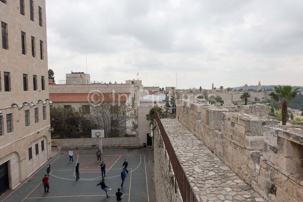 Young people playing football below Ramparts Walk on 31st March 2016 in Jerusalem, West Bank.