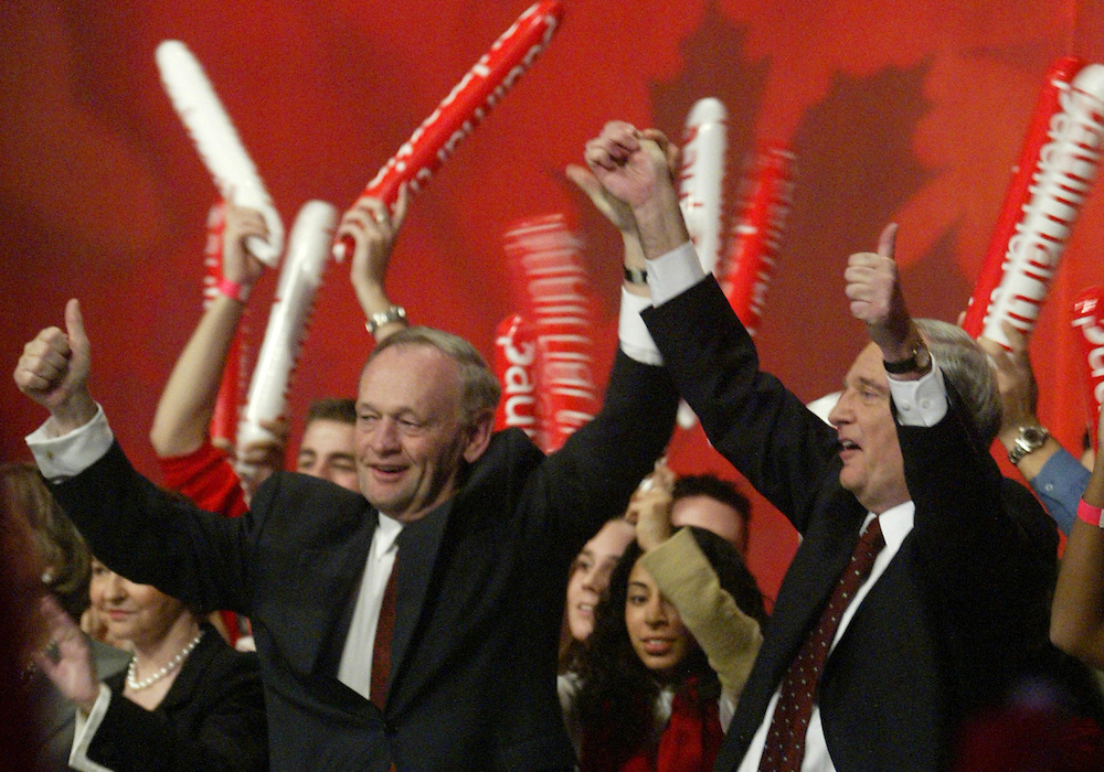 Canadian Prime Minister Jean Chretien (L) waves with Paul Martin before giving his speech at his farewell tribute in Toronto, November 13, 2003. Chretien is<br /> retiring from politics early next year.  REUTERS/Jim Young