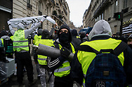 A protester carring a iron pole moving towards the police. More than 125000 gathered in Paris for the Gilets Jaune (Yellow vest) protest. Soon the protest turned violent an protesters clashed with the police, tear gas and flash bombs were fired, many injured and arrested by the police. Paris December 6th 2018. Federico Scoppa