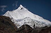 Trekker & crow in silhouette against the spectacular 23,000 foot Himalayan peak of Jichu Drake