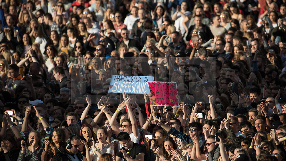 """© Licensed to London News Pictures . 04/06/2017 . Manchester , UK . A placard reading """" Manchester is Supersonic """" and another reading """" One love one heart and one soul """" is held aloft in the audience . The One Love Manchester benefit concert for victims of the Manchester Arena terrorist attack , at the Emirates Old Trafford Cricket Stadium . Ariana Grande, Justin Bieber, Coldplay, Katy Perry, Miley Cyrus, Pharrell Williams, Usher, Take That, Robbie Williams, Black Eyed Peas and Niall Horan are amongst the performers. Photo credit : Joel Goodman/LNP"""