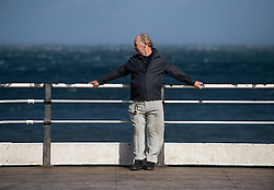 © Licensed to London News Pictures. 12/09/2011..Saltburn Beach, Saltburn, Cleveland, England...A man holds onto the pier railings as he braves strong winds blowing across the beach at Saltburn in Cleveland...Photo credit : Ian Forsyth/LNP