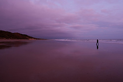 © Licensed to London News Pictures. <br /> 30/10/2016. <br /> Saltburn-by-the-Sea, UK.  <br /> A man walks along the beach at low tide as clouds are lit pink by the first light of the day at Saltburn-by-the-Sea on the north east coast of England.<br /> Photo credit: Ian Forsyth/LNP