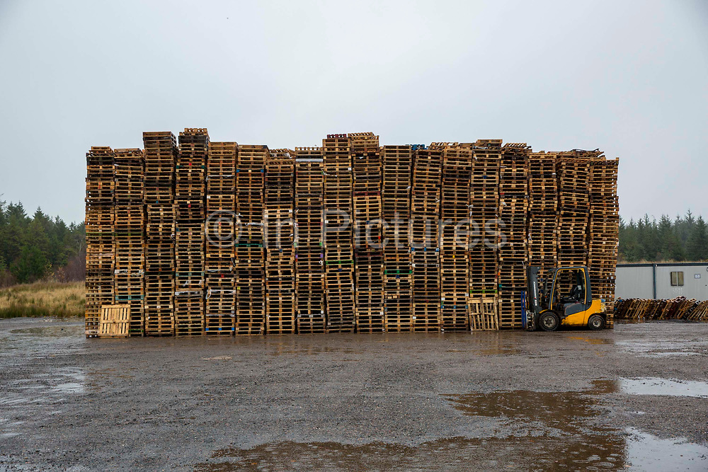A pallet truck parked in front of a large stack of wooden pallets on an industrial site near the M74 on the edge of Happendon Wood near Lanark, Scotland.