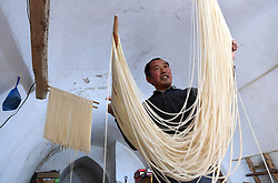 January 30, 2018 - Sanmenxia, China - A villager makes dried noodles in Beiwan village, Caiyuan township, Sanmenxia city of central China's Henan Province. Around 70 households in the village benefited from their handmade traditional dried noodles. (Credit Image: © Zhu Xiang/Xinhua via ZUMA Wire)