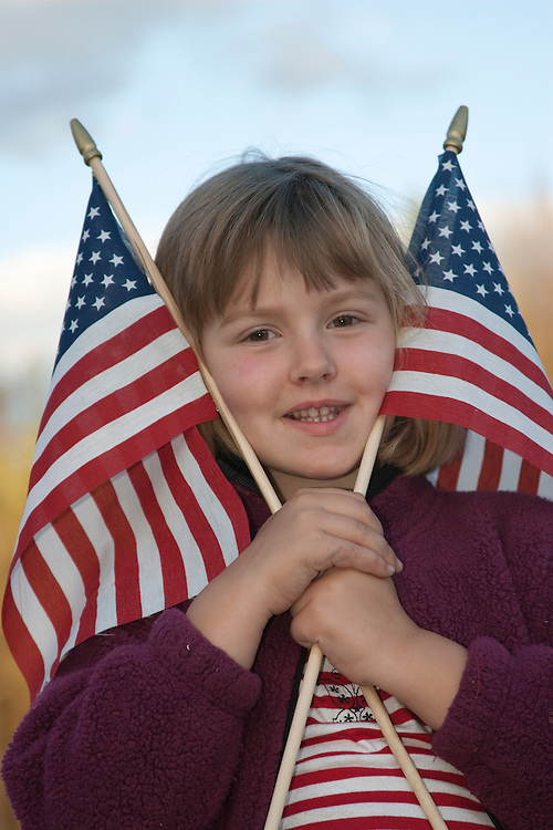 United States, Montana, Flathead River, girl (age 6) with American flags