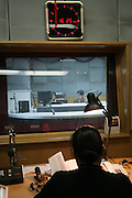 """Radio producer Shanshan watches as announcers sit in a recording boot during the recording the program """"Kejia Xiangqing"""" in Kejia, or Hakka language in Beijing November 19."""