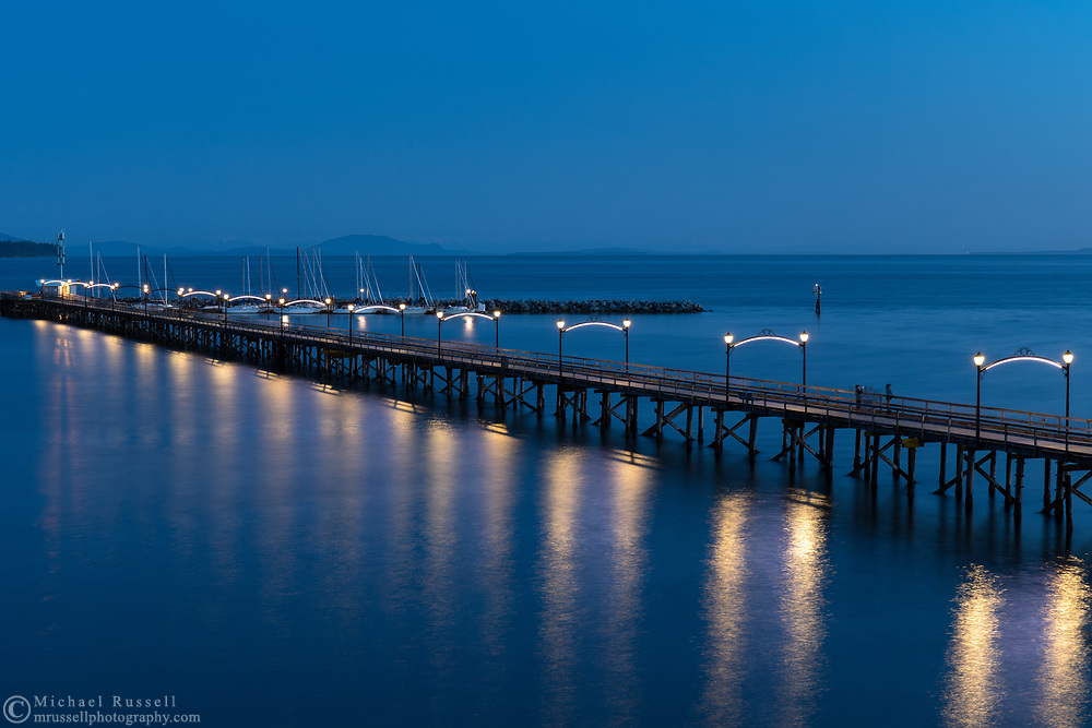View of the White Rock Pier from Marine Drive in White Rock, British Columbia, Canada.  This view looks south over the pier, Boundary Bay, and Semiamhoo Bay in Washington State.  The San Juan Islands are visible in the distance.