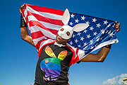 A young man wearing a Playboy bunny t-shirt and white rabbit mask holds an American flag over his shoulders during the Brighton Pride Parade on 6th August 2016 in Brighton in the United Kingdom.