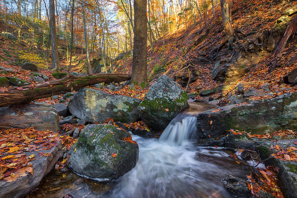 Indian Well State Park and New England fall foliage near Shelton, CT. In this New England landscape photography image fall foliage is framing an Indian Hole Brook cascade providing a view of the entire fall scenery at this spot. Indian Well State Park is only a 25 minute drive from New Haven and rewards with this spectacular New England waterfall. <br /> <br /> Connecticut Indian Well State Park fall scenery photography images are available as museum quality photography prints, canvas prints, acrylic prints or metal prints. Prints may be framed and matted to the individual liking and decorating needs at:<br /> <br /> https://juergen-roth.pixels.com/featured/connecticut-fall-scenery-at-indian-well-state-park-juergen-roth.html<br /> <br /> All high resolution Connecticut photography images are available for photo image licensing at www.RothGalleries.com. Please contact me direct with any questions or request. <br /> <br /> Good light and happy photo making!<br /> <br /> My best,<br /> <br /> Juergen<br /> Prints: http://www.rothgalleries.com<br /> Photo Blog: http://whereintheworldisjuergen.blogspot.com<br /> Instagram: https://www.instagram.com/rothgalleries<br /> Twitter: https://twitter.com/naturefineart<br /> Facebook: https://www.facebook.com/naturefineart