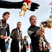 """Mourners pass out flower leis to surfers before a Paddle Out service for the untimely death of Scott Hunt in Wrightsville Beach, NC. Traditional among surfers, a """"Paddle Out"""" is a memorial in which friends and fellow surfers gather in the water, where they hold hands to form a circle, offering prayers and flowers in the waves.  ltqmb  SURFERS MOURN"""
