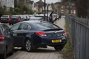 A person squeezes past a mysteriously abandoned Vauxhall car resting at 45 degrees, off the road but blocking a pavement on Ruskin Park, on 2nd February 2018, in Southwark, London, England. Because the car isnt blocking the highway, this is not a police matter - but causing an obstacle on the pavement makes it a council problem.