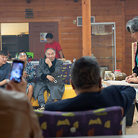 Sharon Nelson, right, demonstrates to the Yakuts tribal members, how they Navajo grind corn and sing a prayer while preparing. The Yakuts delegates visited the facilities in Crownpoint on Monday.