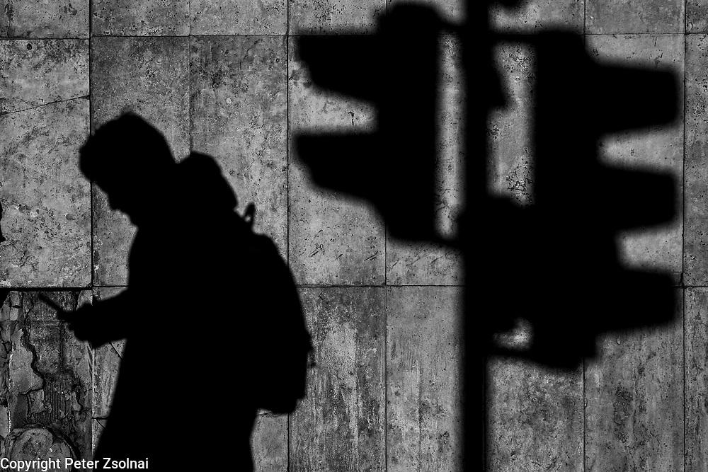 Shadow of a pedestrian walking by a traffic light.