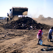 Children walk past their home that is bulldozed down after a shack of fire burnted down dozens or shacks the previous night