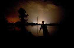 25 Sept, 2005. Cameron, Louisiana. Hurricane Rita aftermath. <br /> Local man Aaron Stokes and his dog Maggie walks into the flooded darkness in Carlyss with a can of gasoline for his boat.<br /> Photo; ©Charlie Varley/varleypix.com