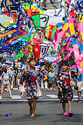 Two young Japanese girls wearing summer kimono called Yukata enjoy Tanabata matsuri in Fussa,, Tokyo, Japan. Sunday August 7th 2016. The Tanabata or star festival is usually celebrated in July though early August more closely follows the traditional calendar. Wishes are tied to wish trees set up in streets and other public places and some areas hold large street parties and parades. The Fussa Tanabata matsuri was started in 1951.