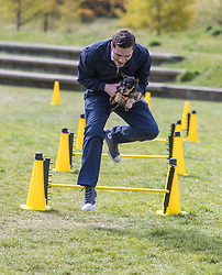 MSPs display their dogs and put them through an agility course with the winner decided by a public vote on the day.<br /> <br /> Pictured: Ross Thomson taking the hurdles holding his dog Poppy