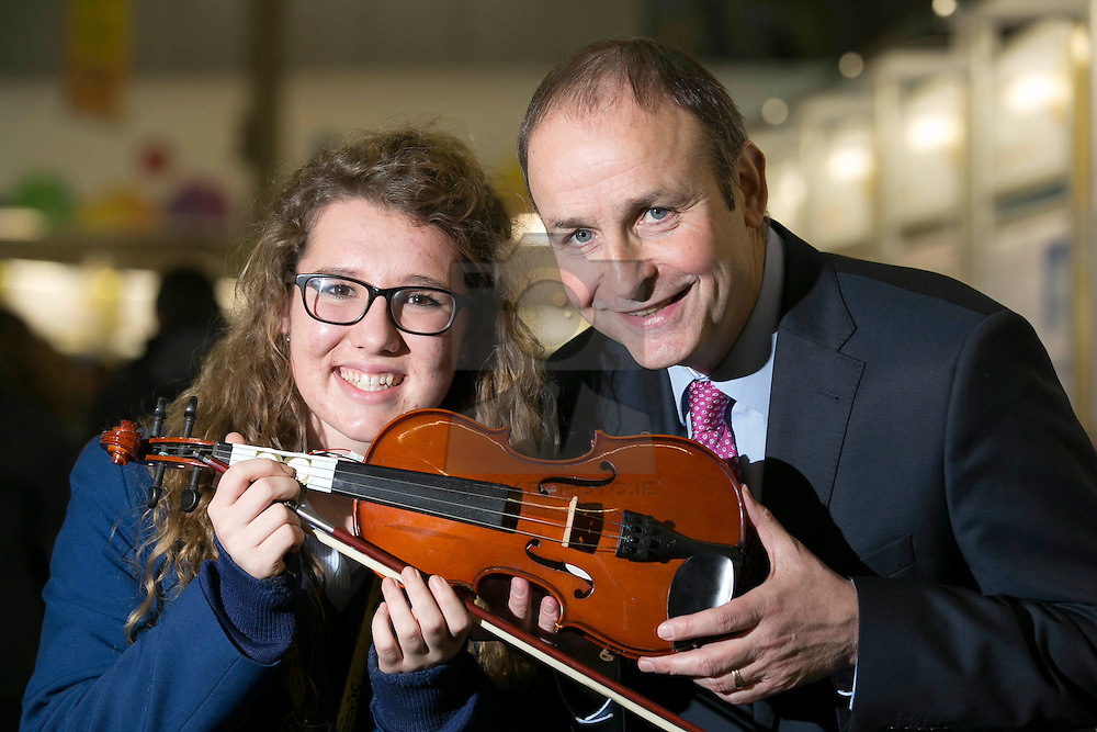 """Repro Free: 08/01/2014 <br /> Fianna Fail leader Micheál Martin TD is pictured with Clare Keaveney-Jimenez from Scoil Mhuire Cork  with her project """"The energy of an orchestra -from notes to volts using piezoelectric technology"""" at the BT Young Scientist & Technology Exhibition 2014 in the RDS Dublin. Picture Andres Poveda"""