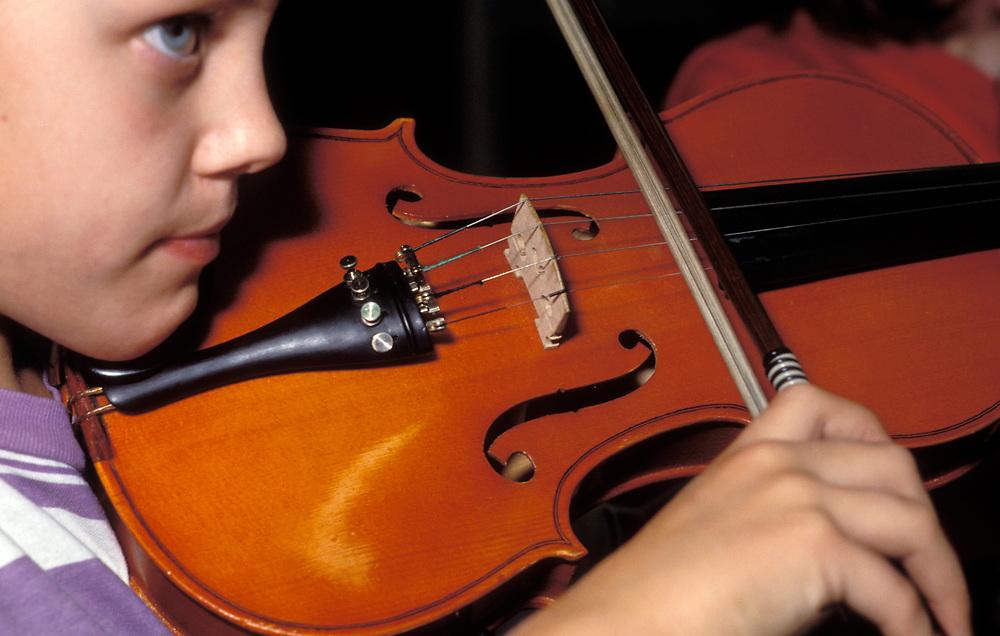 Music class at primary school; UK, Schoolchild playing violin