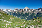 In the alpine meadows of Lötschental above Lauchernalp gondola lift station, see the Bietschhorn (3934 m/12,907 ft) in canton Valais/Wallis, Switzerland, the Alps, Europe. The northeast and southern slopes of the Bietschhorn are in Jungfrau-Aletsch Protected Area, a UNESCO World Heritage Site. Kandersteg is a great base for hiking: an epic hike from Selden in Bern canton traverses Lötsch glacier and Lötschenpass (Lötschepass) to neighboring Lötschental in Valais canton; hiking poles are recommended for snow and rocks. The walk starts with a reserved Postbus ride from Kandersteg to Selden (in Gasterntal / Gasteretal / Gasterental), climbs 1350 meters, descends 925 m, and ends 13 km later at Lauchernalp lift station, which descends to Wiler in Lötschental, to reach Goppenstein via Postbus, back to Kandersteg via train. You can also reverse the route or stay overnight in dorms at Lötschepass hut.
