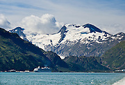 Whittier sits strategically on Kenai Peninsula at the head of Passage Canal, on the west side of Prince William Sound, in Alaska, USA. Whittier is a port for the Alaska Marine Highway System, a ferry service which operates along the south-central coast, eastern Aleutian Islands, and the Inside Passage of Alaska and British Columbia, Canada. Cruise ships stop at the port of Whittier for passenger connections to Anchorage (by road 60 miles) and to the interior of Alaska via highway and rail (the Denali Express). Known by locals as the Whittier tunnel or the Portage tunnel, the Anton Anderson Memorial Tunnel links Whittier via Portage Glacier Highway to the Seward Highway and Anchorage. At 13,300 feet long (4050 m), it is the longest combined rail and highway tunnel in North America. Whittier was severely damaged by tsunamis triggered by the 1964 Good Friday Earthquake, when thirteen people died from waves reaching 43 feet high (13 meters).
