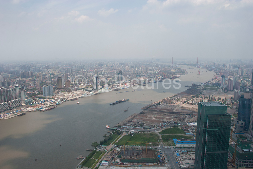 View looking from The Oriental Pearl Tower in Pudong, across the Huang Pu River to Puxi Shanghai's downtown area in Shanghai, China. The Bund's western buildings lines the bottom of the view as modern Shanghai's high-rise skyscraper filled landscape raises up behind.