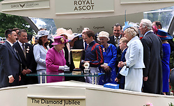 Queen Elizabeth the II presents the trophy for the Diamond Jubilee Stakes to jockey Tom Queally after winning with The Tin Man during day five of Royal Ascot at Ascot Racecourse.
