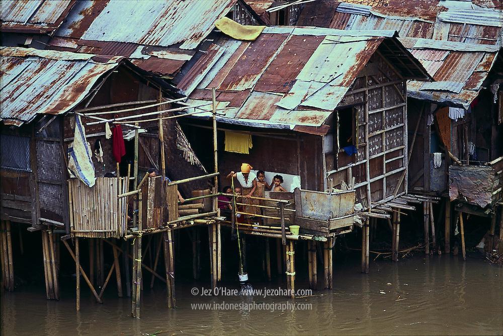 Mother bathing children, Ciliwung river, Jakarta, Java, Indonesia.