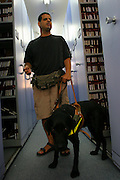Library for the Blind. A blind man and guide dog in the library