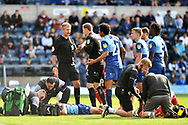 Wycombe Wanderers goalkeeper Ryan Allsop confronts referee Christopher Sarginson as Matt Bloomfield lies injured on the floor after Lincoln had scored,  during the EFL Sky Bet League 1 match between Wycombe Wanderers and Lincoln City at Adams Park, High Wycombe, England on 7 September 2019.