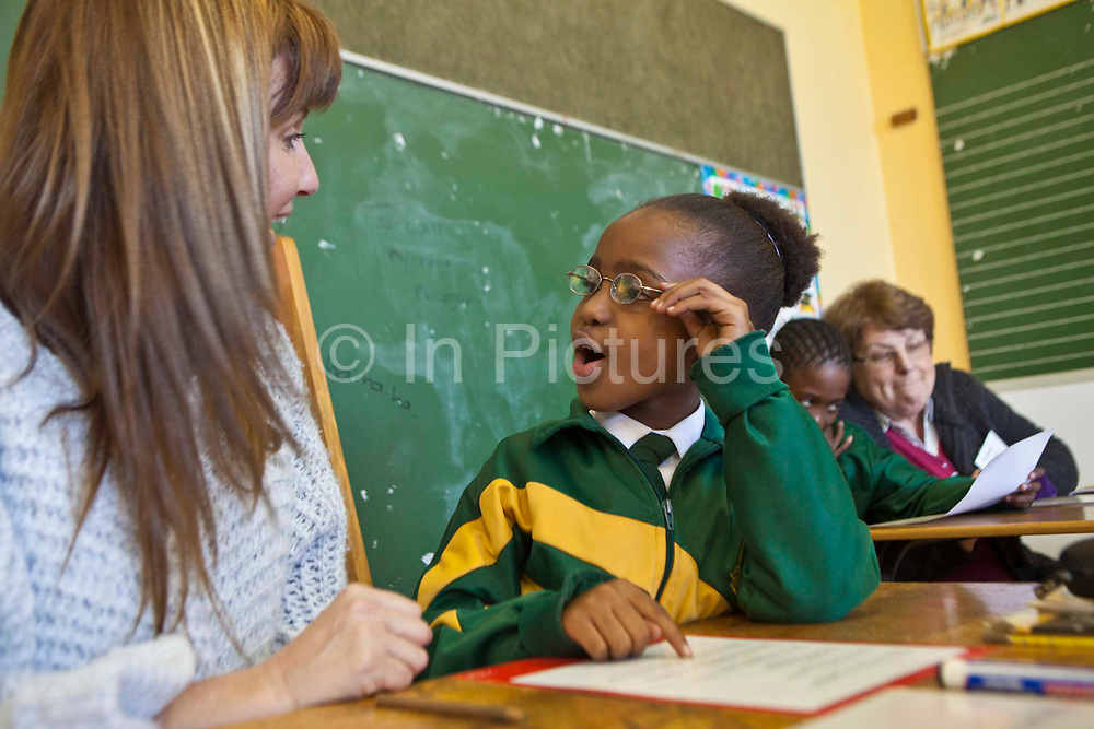 A young African school girl holds her glasses and has a lively conversation with her reading coach in a classroom in Observatory Primary School, Cape Town, South Africa.  She has just successfully read a new word.  Another student and teacher sit together in the background reading. The volunteer teachers have been provided to the school by Shine Centre which is a charity that aims to address the high illiteracy rate in South Africa by improving literacy levels among children in schools and disadvantaged communities.