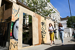 © Licensed to London News Pictures. 22/08/2019. London, UK. Women walk past a residential property which has been boarded ahead of the 2019 Notting Hill Carnival in West London, which takes place this bank holiday weekend. Up to 1 million people are expected to attend the biggest street party in Europe. Photo credit: Dinendra Haria/LNP