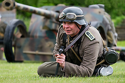 A reenactor from the Nww2A takes part in a Battle re-enactment portraying a member of 21st Panzer Division. Hi lays infron of a German PAK Anti Tank Gun holding and MP40 machine pistol <br /> during an event held at Fort Paull Humberside in may 2019<br /> <br /> Copyright Paul David Drabble<br /> 5th & 6th May 2019<br /> www.pauldaviddrabble.co.uk