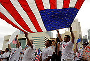 Nicolas Vergara (right) holds an American flag with other participants of the MegaMarch for Immigration Reform, in front of Dallas City Hall May 01, 2010
