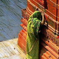 "Asia, India, Varanasi. A Hindu woman prays at the ochre-colored Durga or ""monkey"" temple in Varanasi."