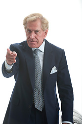 mature man in a suit pointing his finger at someone