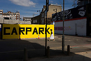 A woman walks past a large yellow car park sign on street in Shoreditch, East London. Striding across the road, the lady wears a white skirt and espadrilles with high heels. It is later in the afternoon on this warm summer's day and the sun has partly covered the yellow sign with its black lettering, written as one word rather than the normal two. Otherwise, the street is empty of other pedestrians but this area is undergoing massive regeneration thanks to the new Crossrail project, a part of which is seen as a concrete overpass for trains in the background.
