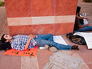 16 OCTOBER 2011 - PHOENIX, AZ: An Occupy Phoenix protester rests on a sidewalk in downtown Phoenix, AZ, Sunday. About 200 people continued the Occupy Phoenix protest in downtown Phoenix Sunday afternoon. The protest peaked Saturday afternoon at about 2,000 people. Nearly 50 people were arrested late Saturday night on misdemeanor trespassing charges when they tried to camp in a park near downtown and on Sunday the crowd dwindled to 200. Protesters hope to continue the protest through Monday by marching around downtown and picketing banks in the area.   PHOTO BY JACK KURTZ